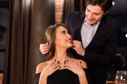 Romantic gift. Cheerful woman getting luxury necklace from her husband on Valentine's day