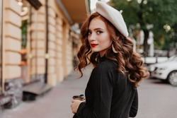 Romantic ginger woman in french beret looking back. Outdoor photo of adorable brunette girl enjoying autumn day.