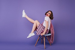 Romantic girl in white shoes sitting on chair and laughing in studio. Indoor shot of carefree curly woman posing on purple background with sincere smile.