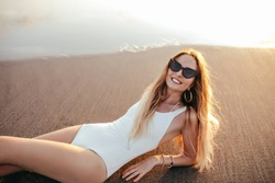 Romantic girl with beautiful smile lying on the sea coast. Outdoor shot of lovely european female model in white swimsuit posing on the ground near ocean waves.