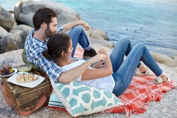 Romantic, happy couple during a picnic on the rocks, near the ocean