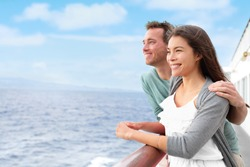 Romantic happy couple on cruise ship on boat travel embracing looking at view. Happy lovers traveling on vacation sailing on open sea ocean enjoying romance. Young Asian woman and Caucasian man.