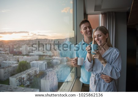 romantic happy young couple enjoying evening coffee and beautiful sunset landscape of the city while standing by the window #1025862136