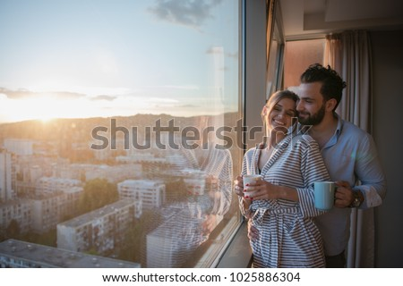 romantic happy young couple enjoying evening coffee and beautiful sunset landscape of the city while standing by the window #1025886304