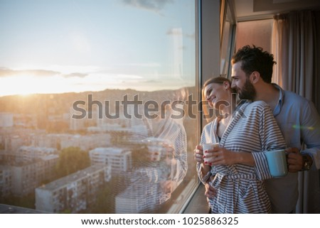 romantic happy young couple enjoying evening coffee and beautiful sunset landscape of the city while standing by the window #1025886325