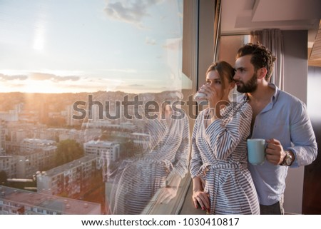 romantic happy young couple enjoying evening coffee and beautiful sunset landscape of the city while standing by the window #1030410817