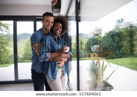 romantic happy young multiethnic couple enjoying morning coffee by the window in their luxury home #557604061