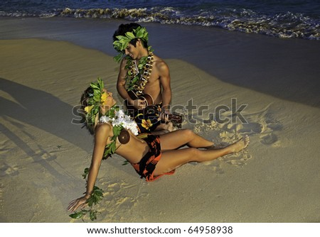 romantic hawaiian hula couple on the beach at sunrise with the man playing ukulele