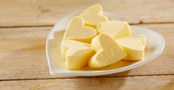 Romantic heart shaped butter pats on a matching white plate in a close up low angle view on wood in a food styling concept