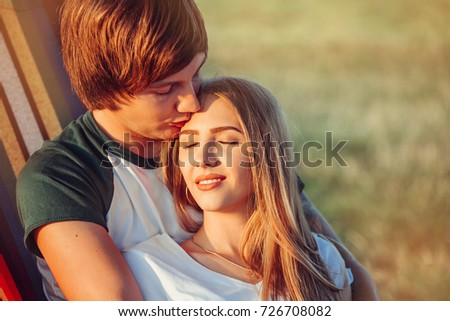 Romantic hipster couple enjoy rest on a hammock in the park, cute woman lying with handsome man. Holidays, vacation concept - smiling couple having fun outdoors in summer
