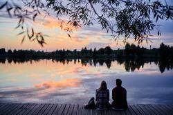 Romantic holiday. Young loving couple sitting together on lake bank enjoying beautiful sunset.