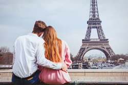 romantic holidays in France, couple sitting together near Eiffel tower in Paris, honeymoon travel