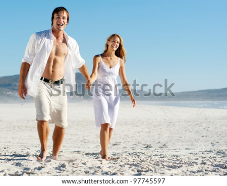 romantic honeymoon couple walk on the beach during a tropical summer holiday vacation. carefree stress free lifestyle concept.