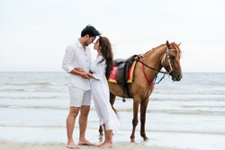 Romantic honeymoon of Asian couple - Handsome man and asian woman kissing on beach during romantic honeymoon travel. The couples are doing horse riding.