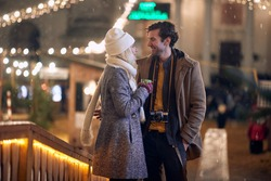 romantic image of young caucasian couple at christmastime, talking outdoor, standing close