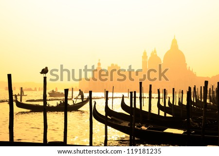 Romantic Italian city of Venice (Venezia), a World Heritage Site: traditional Venetian wooden boats, gondolier and Roman Catholic church Basilica di Santa Maria della Salute in the misty background.