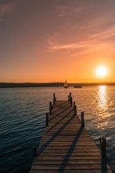Romantic landscape: Sunset over the lake, bridge and boats