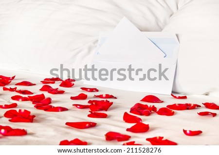 Romantic letter - an envelope lying on a bed among rose petals and pillows