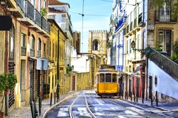 Romantic Lisbon street with the typical yellow tram and Lisbon Cathedral on the background