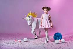 Romantic little girl in beautiful pink dress. Origami and minimalism. Fashion children. Designer collection. White big unicorn origami made of paper.