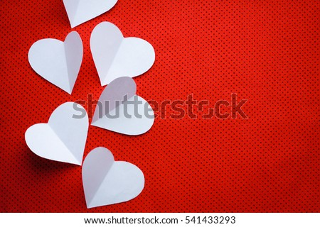 Romantic love concept background with copy space for text and three white paper hearts laying on a red textured background in a small black polka dots. Beautiful Valentines minimalist hipsters card. #541433293