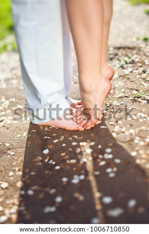 Romantic love date. St. Valentine's Day. The girl is standing on her feet favorite. Sunny day. The petals of flowers around #1006710850