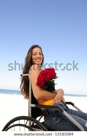 romantic love: happy woman in wheelchair with red roses