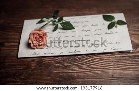 Romantic love letter and rose. Vintage retro background with love letter and rose on wood. Valentine�s day background.