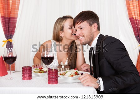 Romantic lovers sitting at an elegant restaurant table enjoying a meal and sharing secrets whispering to each other