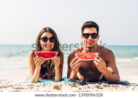 Romantic lovers young couple relaxing holding and eating a slice of watermelon on the tropical beach.Summer vacations #1390096328