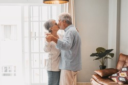 Romantic loving senior couple holding hands enjoying dancing together while kissing each other in the living room of house, couple kissing and embracing while holding hands together at home