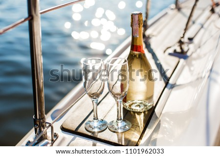 Romantic luxury evening on cruise yacht with champagne setting. Empty glasses and bottle with champagne and tropical sunset with sea background, nobody.