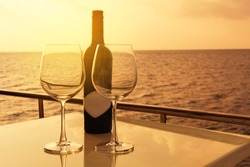 Romantic luxury evening on cruise yacht with winery setting. Glasses, red wine bottle and tropical sunset with sea background, nobody.