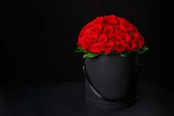 Romantic luxury red roses in a black gift box with space for logo on a black background studio,studio photography,spring is coming,international women's day