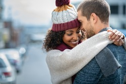 Romantic man and woman embracing outdoor in autumn. Happy boyfriend and smiling african girlfriend head to head on city street with copy space. Young couple loving during a romantic getaway in winter.