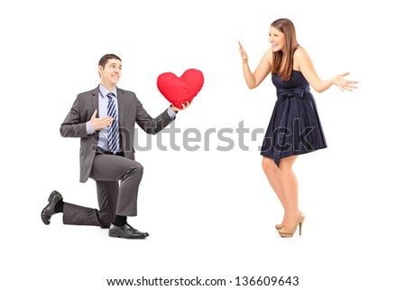 Romantic man giving a red heart to a young woman, isolated on white background