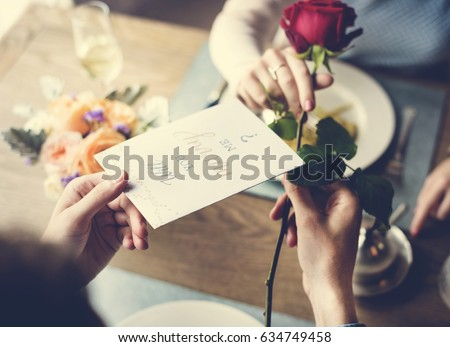 Romantic Man Giving Will You Marry Me Card with a Rose to Propose Woman