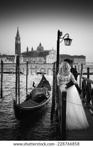 Romantic married couple in Romantic Italian city of Venice in black and white. Traditional Venetian wooden gondola and Roman Catholic church of San Giorgio Maggiore in the background.