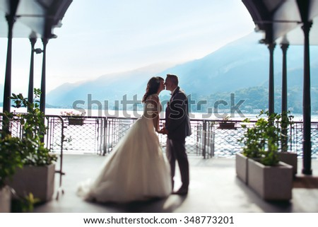 Romantic married couple kissing at port lake and mountains background #348773201