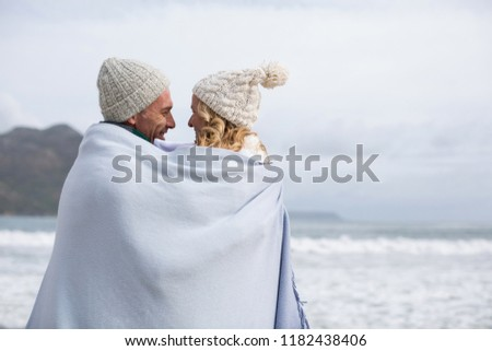 Romantic mature couple wrapped in blanket on the beach