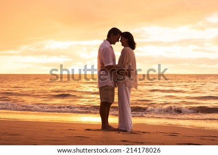 Romantic Middle Aged Couple in Love Embracing on the Beach at Sunset