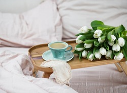 Romantic morning.A coffee table in a pink bed, a Cup of coffee and flowers on the table. Valentine's day.