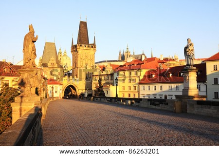 Romantic morning View on the Prague gothic Castle and St. Nicholas' Cathedral with the Charles Bridge baroque Statues, Czech Republic