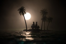 Romantic night scene. Fantasy night landscape with little island with palms and full moon over sea. Creative table decoration. Silhouette of romantic couple on uninhabited island. Selective focus.
