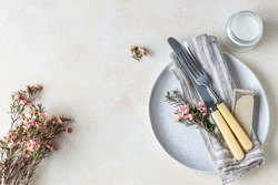Romantic or spring table setting. Knife and fork, little pink flowers and linen napkin on a plate, light concrete background. Flat lay. Selective focus.