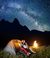 Romantic pair lovers looking to the shines starry sky and Milky way in the camping at night near campfire. On the background silhouette of the high mountains. Low light