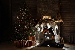 Romantic photo of a couple in love that is hugging sitting on the floor near the fireplace and Christmas tree