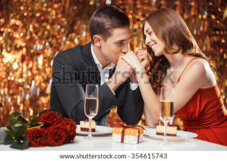Romantic photo of beautiful couple on glitter gold background. Couple having date at Valentine\'s Day. Lovers having dinner. There are glasses with champagne, desserts, roses and gift on table