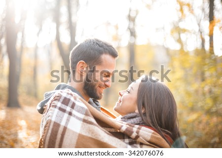 Romantic photo of cute couple outdoors in fall. Young man and woman standing with blanket and smiling