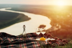 Romantic picnic in nature with panoramic background. The beauty of the setting sun, fresh fruits, cheese and wine. Romantic dinner outdoors. Picnic on the hill at sunset with river background.